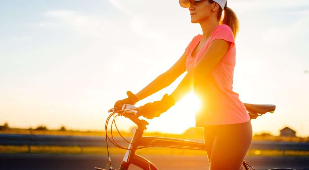 Portrait of beautiful muscular woman holding grips of bike steering bar on sunny summer day in sunset, after exhausting ride. Woman is wearing cap and dressed in sports clothing. Location: Novi Sad, Serbia, Europe